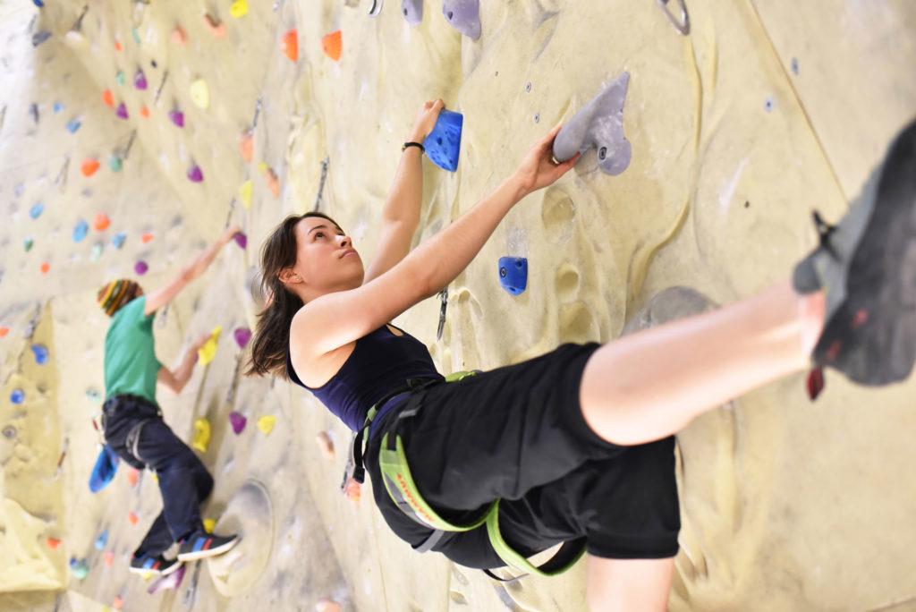 Junge Frau an Kletterwand